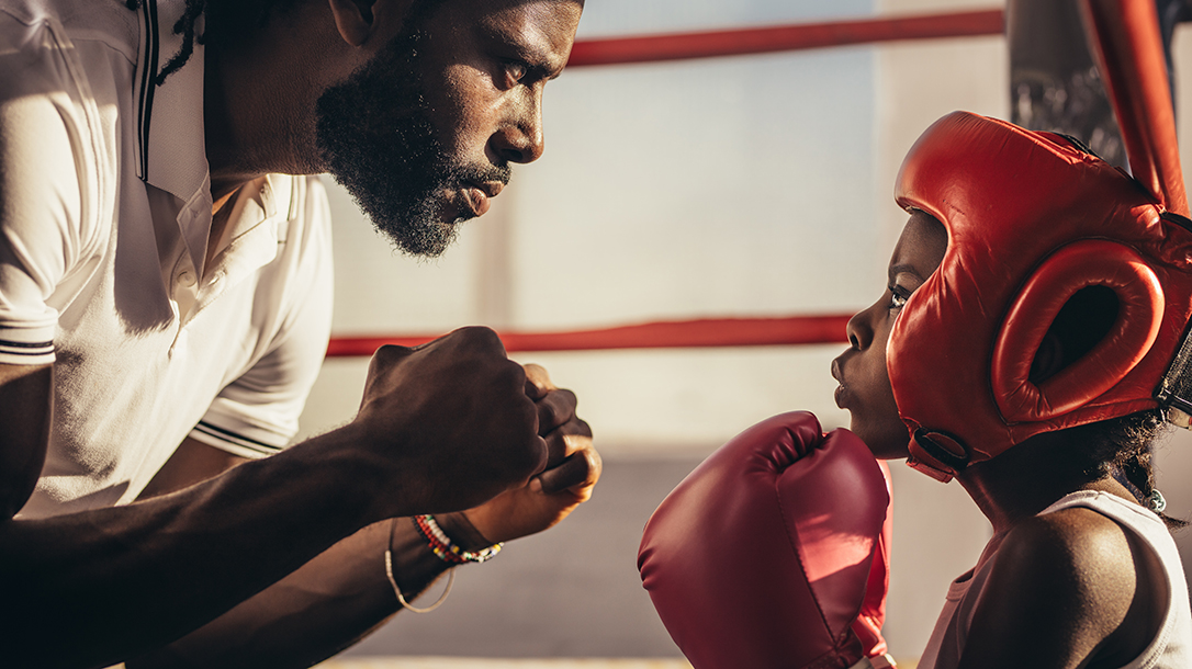 Manning Up, Coach teaching a boy how to box.