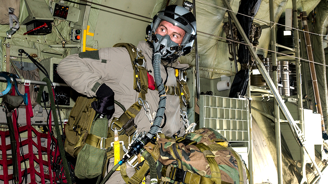 Travis Haley checking gear before a jump at high altitude.