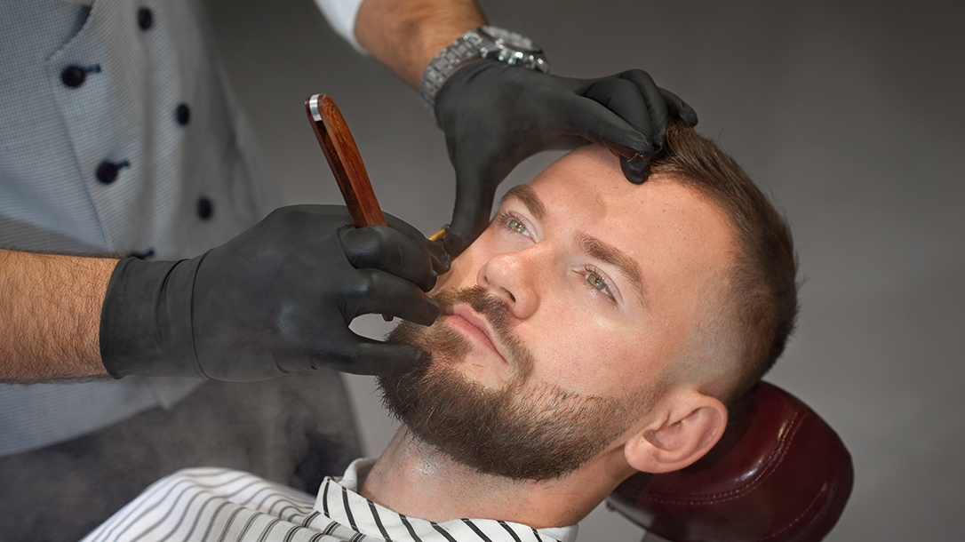 A man gets a straight razor shave from a qualified barber.